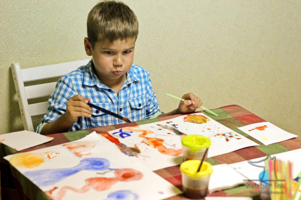 Мальчик с кисточками рисует кляксы