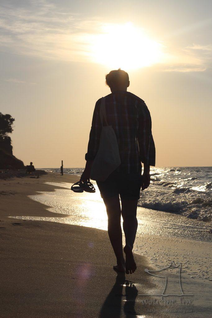 Девушка на рассвете идёт по берегу моря