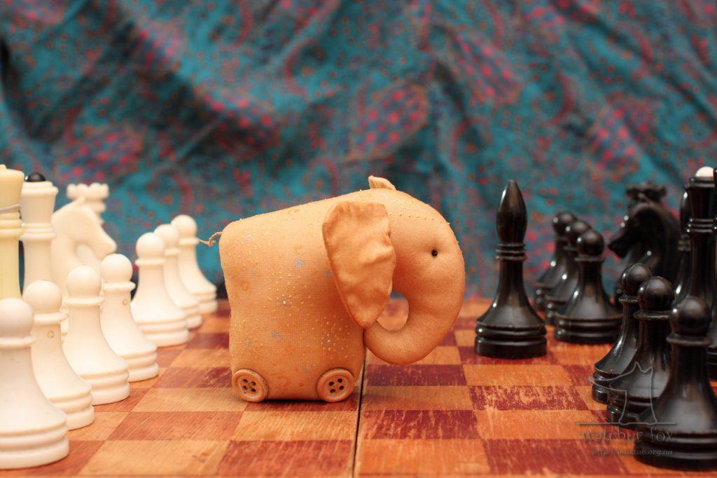 Игрушечный слон на шахматной доске